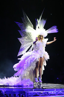 Lady Gaga wearing a white gown with a headdress and wings