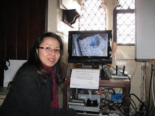 Jennie Mak inside the ringing-chamber of Derby Cathedral with a female peregrine visible in the monitor behind her