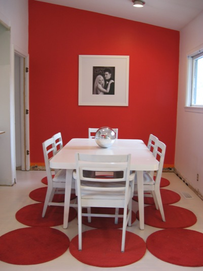 Elegant-modern-interior-design-dining-room-with-white-dining-table-white-chairs-red-circles-rug-red-and-white-walls-and-picture