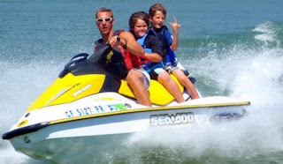 Aloha Beach Camp Counselor Trevor Kilroy gives a couple Aloha Beach Camp kids a jet skiing ride at Castaic Lake. Castaic Lake is just outside Los Angeles near Magic Mountain in Castaic. When Aloha Beach Camp kids go to the lake, they can jet ski, swim, go tubing, wakeboarding and boating. All campers wear coastguard-approved life vests at all times.
