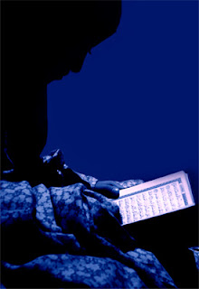 A girl is profiled against a backdrop of blue, her head bent over a Koran.