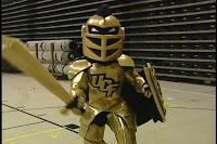 Golden Knight mascot of UCF sports teams in full armor holds a shield and points a sword at the camera while standing in a basketball gymnasium.