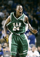 One UAB basketball player wearing a green uniform yells in celebration against a backdrop of fans in an arena.