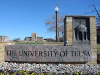 Stone and marble sign that says The University of Tulsa with under a blue sky.