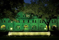 A green lit prestigious stone building at night with an illuminated sign in the front reading Tulane University.