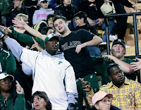 numerous male fans wave while wearing Tulane University gear in the stands of an event.