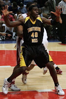 Southern Miss basketball player in black uniform posting up beneath the basket.