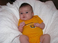 baby on pillow wearing gold Southern Miss onesie