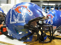 Shiny blue University of Memphis helmet with a black face mask and artwork of the Memphis Tiger jumping over a blue letter M.