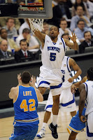 A University of Memphis basketball player in a white uniform elevating to slam dunk over former UCLA player Kevin Love.