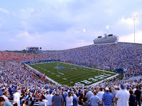 View from the stands of fans at a crowded Memphis Tiger football game on a cloudy day.