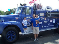 A father with two young children standing in front of a blue University of Memphis themed firetruck.