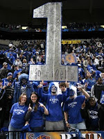 Four University of Memphis fans holding a giant silver number 1 sign at a basketball game.