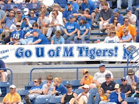 An outdoor event with fans in the stands hanging a Go U of M Tigers banner at the game.