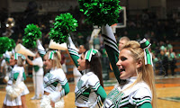 Four Marshall University cheerleaders raising green pom poms at a basketball game.