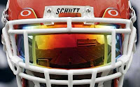 Orange football helmet with white face mask with orange visor in the face mask reflecting a football field.