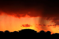 Orange sunset with rain clouds releasing water over a black silhouette of Spanish buildings below the sunset.