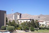 Spanish style academic buildings with a desert mountain in the background and limited green landscaping in the foreground.