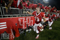 Houston football players high five fans.