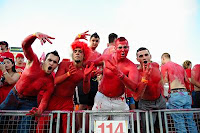UH students paint their chests red at football game.