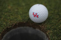 University of Houston golf ball next to golf hole.