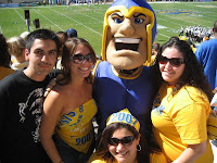 San Jose Spartan mascot in stands with fans at a football game.