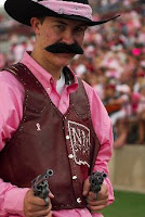 New Mexico State mascot live cowboy with mustache dressed up at football game with guns.