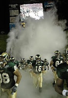 Colorado State Rams football players run onto field through smoke.