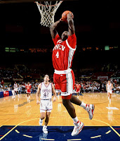 Larry Johnson dunks in red UNLV uniform in college basketball game.