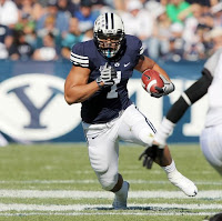 Strong BYU football player runs the ball down field.