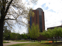 A tall brick building on the Memphis campus surrounding with green leafy trees.