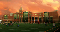 Marshall University practice football field in front of a two story brick athletic building under an orange sky.