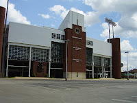 Exterior view of the Marshall University brick football stadium underneath a cloudy sky.