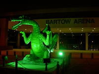 Illuminated green dragon statue in front of Bartow Arena athletic facility.
