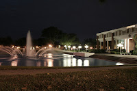 Large water spouting fountain neighboring a two story colonial white building under a dark night sky at UCF.