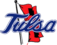 Cursive blue letters spelling Tulsa with a red flag on a black flag pole.