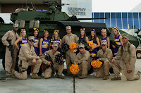 ECU cheerleaders with soldiers in front of tank.
