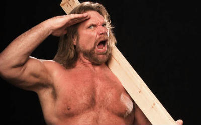 """Hacksaw"" Jim Duggan saluting and holding 2x4"