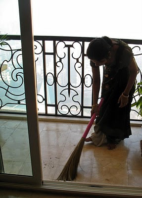 maid sweeping floor in apartment in India