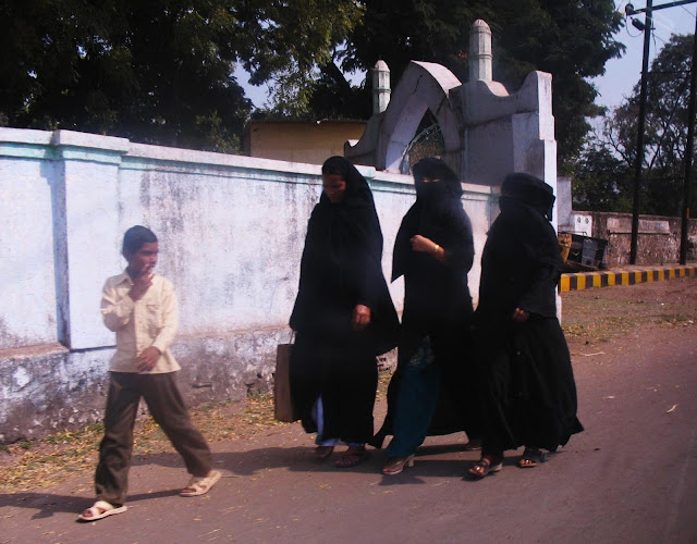 burqa women with little boy walking ahead