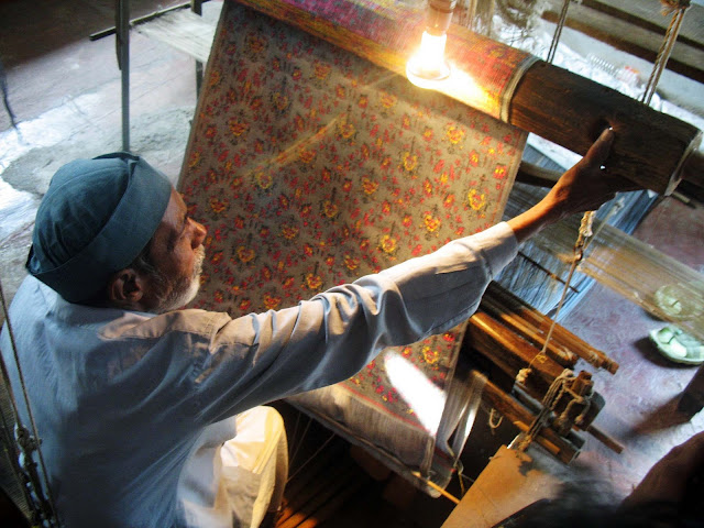 Indian weaver with tapestry