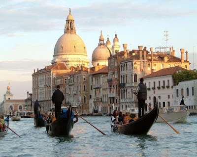 Gondoliers plying the lagoon before San Marco Basilica, Venice