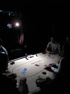 Benjo's photo of the tourney staff using flashlights to enable players to complete hands
