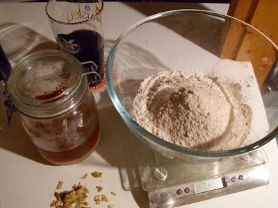 Bowl with flour, scattering of hops, yeast in a jar, beer in a glass
