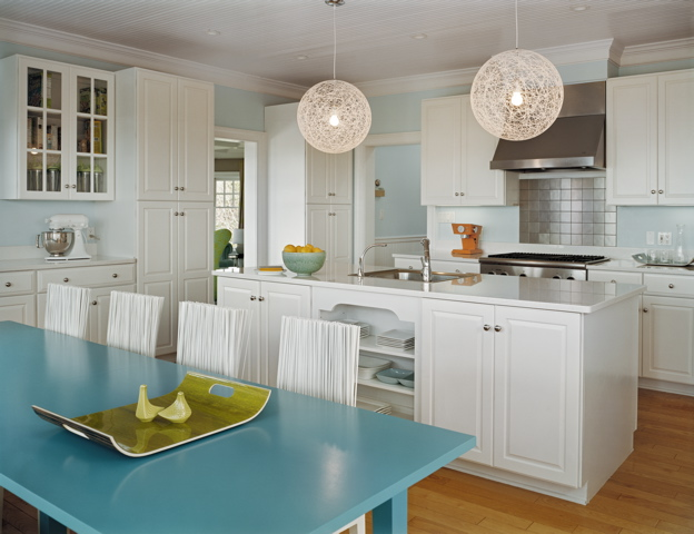 Eat in kitchen by Ghislaine Vinas with white cabinets, stainless steel square tile backsplash, round pendant lights, light blue walls and a long turquoise dining table surrounded by modern white chairs