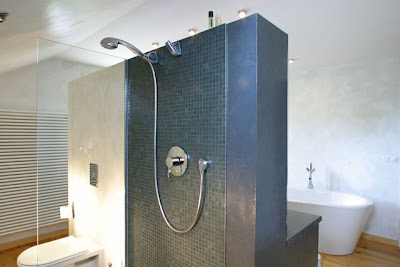 Ultra modern spa like bathroom with stand alone tub and tile shower with glass walls