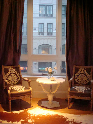 Sitting area in a NYC loft with antique chairs upholstered in Silk Trading Co. fabic, a white cow hid rug, white antique table and long silk purple curtains