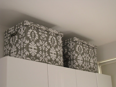 Brocade print storage boxes on top of white cabinets in a London kitchen