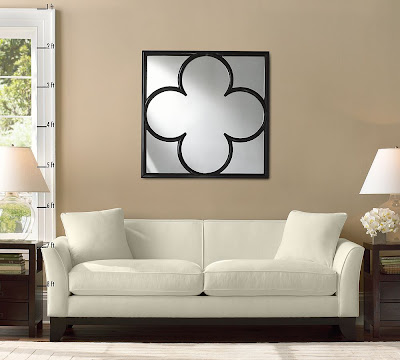 Black finish wood frame quatrefoil wall mirror from Pottery Barn in a living room with a white sofa and two wood end tables