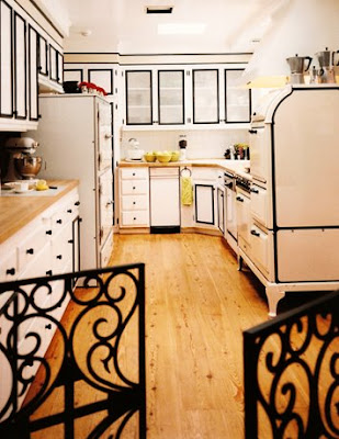 Kitchen by Jeff Andrews Design with white cabinets with black borders and trim, white drawers with black pulls and wood block countertops and floor